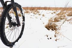 The front wheel of mountain bike in the first snow. stock image