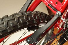 Detail of the bike. The front wheel of the red bicycle with visible V-brake stock photo
