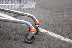 Front wheels of shopping cart. The front wheels of a shopping cart in a store parking lot royalty free stock images