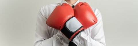 Businessman wearing red boxing gloves. Front wide view of businessman wearing red boxing gloves with his arms crossed over his chest stock images