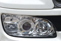A front width headlight assembly unit on a white painted luxury car Royalty Free Stock Photo
