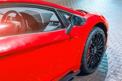 Front wing and the wheel of the car are a supercar, at night in a parking lot in the city. Front wing and the wheel of the car are a supercar, at night in a Stock Photo