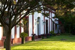Front yard of Argentinian ranch house in late afternoon. A summertime shot of an Argentinian farm house or ranch house in the late afternoon. A leafy tree in the Royalty Free Stock Photos