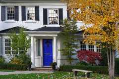 Front yard in fall. House with portico Royalty Free Stock Image