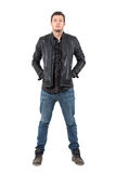 Front of young man in jeans and jacket with hands in pockets looking at camera. Stock Photo