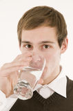 Man drinking water. Frontal head-and-shoulder view of a young man in a white shirt and brown vest a glass of water drinking with looking at camera Stock Photography