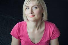 Frontal headshot portrait of mature woman wearing fuchsia shirt Royalty Free Stock Photography