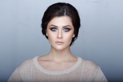 Headshot portrait of sensual brunette girl with amazing green eyes, perfect make-up, looking at camera. Gray background. royalty free stock photos