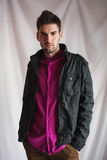 Frontal portrait of a handsome young man with a beard in a purple shirt and a black jacket Stock Photography