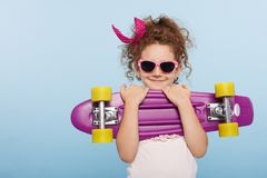Portrait of a fun face of a little girl in pink sunglasses, holding skate in hands, isolated on a blue background. royalty free stock photo