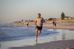Athletic fit and strong runner man training on Summer sunset beach in sea shore running and fitness workout in sport and healthy l. Frontal portrait of young Royalty Free Stock Images