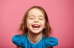 Frontal shot of laughter joyful little girl stands beside pink wall. Funny emotional kid portrait photo Royalty Free Stock Photo