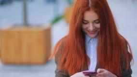 Frontal sikt av den nätta le ungdomliga rödhåriga flickan i brunt omslag och vitt-skjortan som communcating via henne arkivfilmer