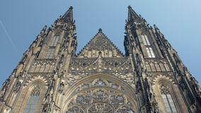 Frontal tilt up view of facade of ancient gothic church St Vitus cathedral in Prague. In sunny day stock video footage