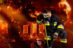 The firefighter is powerless in extinguishing aggressive flame, being all in ash. stock photo