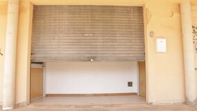 Frontal view of metal shutter of a business closing due to the crisis