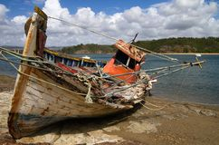 Old broken fishing boat wrecked against the river Royalty Free Stock Image