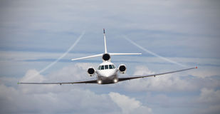 Frontal view of a private jet in midair. With contrails Royalty Free Stock Photos