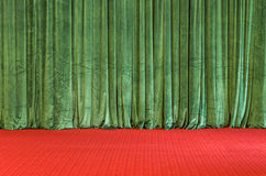 Green Curtains on a red Stage. Frontal view of a theater stage with red velvet floor and grren curtains Stock Image