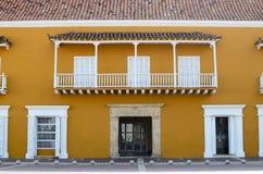 Frontale mening van geel huis met wit deuren, venster en balkon Royalty-vrije Stock Afbeelding