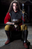 Frontale Mening van Ridder With Sword Sitting tegen Steenmuur Stock Foto's