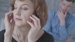 Fronte alto vicino della donna triste elegante matura senior che tiene la sua testa nella priorità alta Figura vaga dell'uomo ner video d archivio