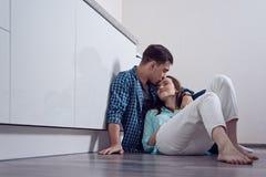 Fronte baciante della donna del giovane che si siede sul pavimento in cucina bianca, relazione, famiglia, amore, inaugurazione di immagine stock libera da diritti