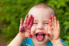 Fronte del bambino del ritratto sporco dai mirtilli Immagine Stock