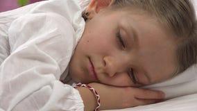 fronte del bambino di sonno 4K a letto, ritratto triste della ragazza, riposante nella camera da letto a casa video d archivio