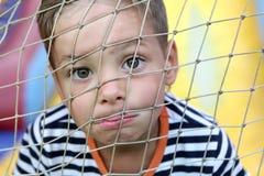 Fronte del bambino dietro rete fotografia stock libera da diritti