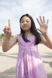 Fronte del dito asiatico di manifestazione della ragazza che funge da simbolico del numero Fotografia Stock