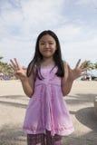 Fronte del dito asiatico di manifestazione della ragazza che funge da simbolico del numero Fotografie Stock