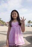 Fronte del dito asiatico di manifestazione della ragazza che funge da simbolico del numero Immagini Stock