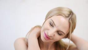 Fronte del primo piano della donna bionda europea attraente che sorride e che gioca con i suoi capelli archivi video