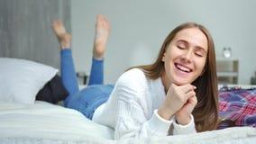 Fronte del primo piano della ragazza felice divertendosi menzogne sul letto in camera da letto che gode e che si rilassa stock footage