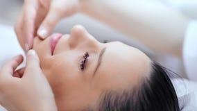 Fronte del primo piano di bella giovane donna con pelle pura durante il massaggio della linea più bassa del mento archivi video