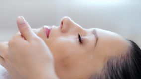 Fronte del primo piano di giovane bella donna che si rilassa e che gode del massaggio di contorno di bellezza alla clinica archivi video