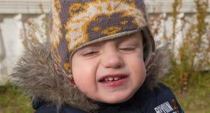 Fronte del ragazzino in un cappuccio caldo con gli occhi e la a coperti Fotografia Stock Libera da Diritti