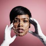 Fronte del ` s della donna di bellezza nelle mani di un medico Fotografia Stock