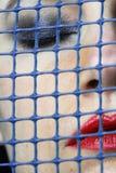 Fronte del ` s della donna dietro una griglia Immagini Stock