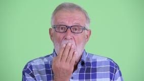 Fronte dell'uomo barbuto senior dei pantaloni a vita bassa che sembra colpito e che copre bocca video d archivio