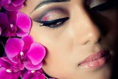 Fronte della bella donna con i fiori dell'orchidea Immagini Stock