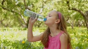 Fronte della bottiglia di acqua della bevanda della ragazza al parco di verde di estate stock footage