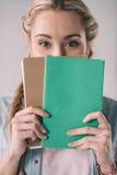 Fronte della copertura della studentessa con i taccuini in mani Fotografie Stock