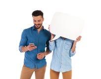 Fronte della copertura della donna con il fumetto mentre l'uomo sta mandando un sms a Immagine Stock
