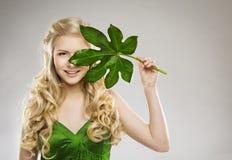 Fronte della donna e foglia di verde, trattamento dei capelli e cura di pelle organici Fotografia Stock