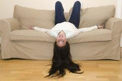 Fronte della donna giù su uno strato mentre sorrisi Fotografie Stock