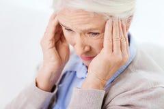 Fronte della donna senior che soffre dall'emicrania Fotografie Stock