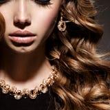 Fronte delle donne del primo piano con i gioielli lunghi dell'oro e dei capelli ricci Fotografia Stock