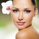 Fronte di bella donna con un fiore bianco dell'orchidea Fotografie Stock Libere da Diritti